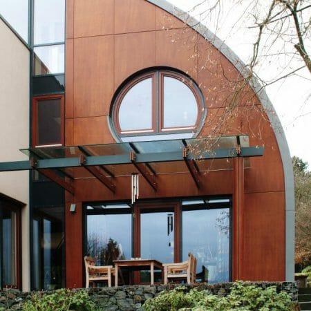 Die ungewöhnliche Hausform wird durch die individuell angefertigten Holzfenster unterstrichen.