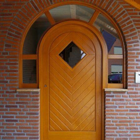 Segmentbogen als Oberlicht mit halbrunder Holztür und Sperrholzaufdopplungen im Fischgrätmuster.
