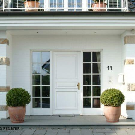 Repräsentative Haustüranlage in weiß mit seitlichen Fenstern.