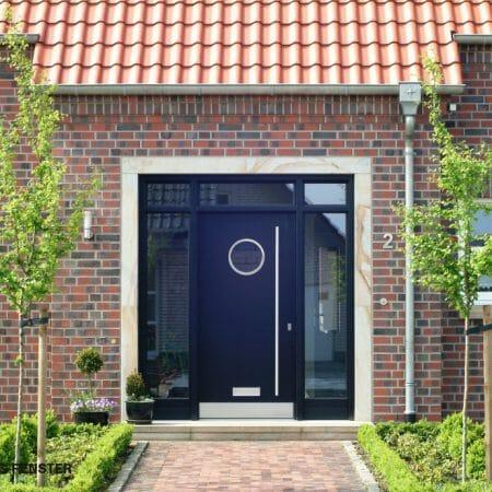 Haustür von Glasfenstern eingefasst. Kreisrunder Lichtausschnitt in der Tür.