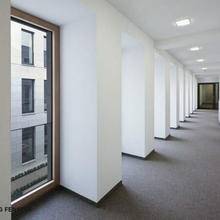 Eine Absturzsicherung aus Glas sorgt für maximale Transparenz sowie maximale Sicherheit der Holz-Aluminium Fenster.