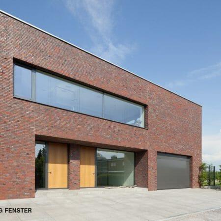 Die von BRÖCKING FENSTER gefertigten Haustüren aus eichenholz sorgen für einen angenehmen Kontrast zu den Aluminum-Fensterelementen.