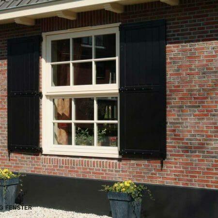 Ein Vertikalschiebefenster mit passenden Fensterläden.