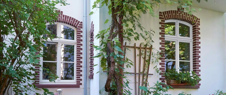 klassische Stichbogenfenster aus Holz mit Sprossen